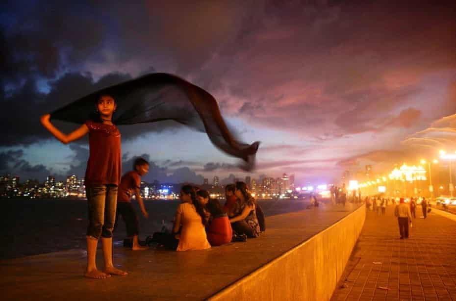 A girl dries a sari following rains on Marine Drive along the Arabian Sea in Mumbai, India,