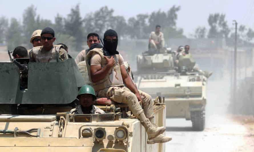 Egyptian armoured vehicles patrol the town of Sheikh Zuweid, Sinai, earlier this month after four soldiers were killed by a roadside bomb. Hundreds of the armed forces have been killed in the peninsula.