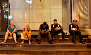 Two Western tourists sit next to Thai police officers using their mobile phone at a closed shopping mall near the bomb outside the Erawan Shrine in central of Bangkok