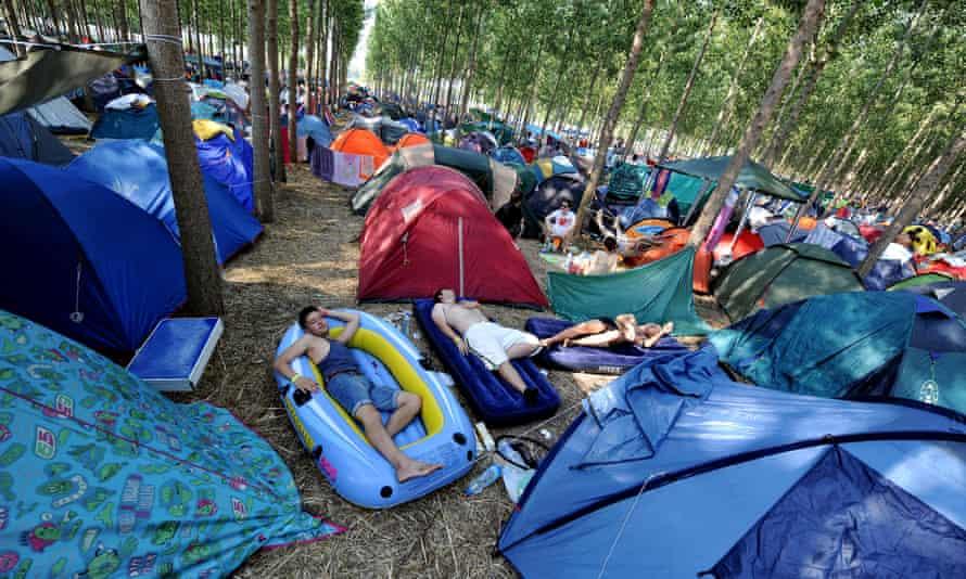 Festival goers sleep among tents at the EXIT festival camp near the Serbian city of Novi Sad