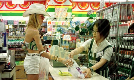 woman serves a customer in a convenience store in tokyo