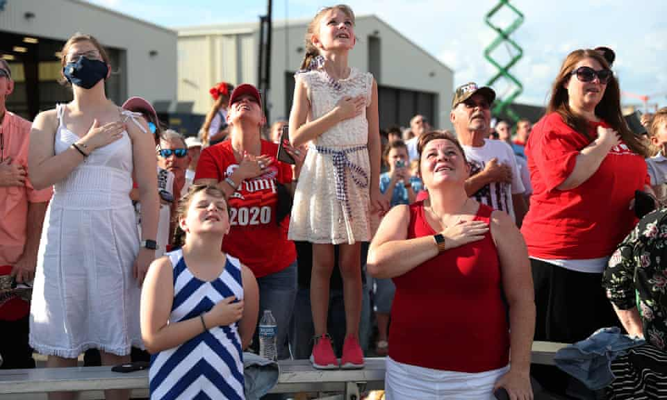 People stand for the Pledge of Allegiance before the arrival of US president Donald Trump for 'The Great American Comeback Rally' at Cecil Airport, Florida on 24 September.