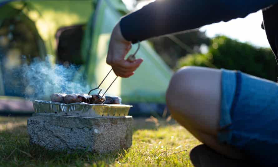 person using a portable bbq with food on top of a stone and in front of a tent