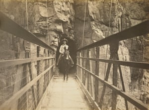 Mule and rider exiting crossing the Kaibab suspension bridge, circa 1930.