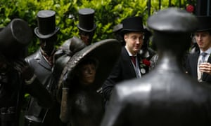 A racegoer stands among the statues at Ascot.