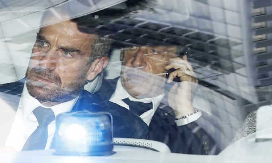 Sarkozy (right) is driven away from court in Paris