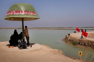On the Talaieh memorial, a man from the Basij militia, an Iranian volunteer force, takes shelter from the sun under a reproduction of a military helmet