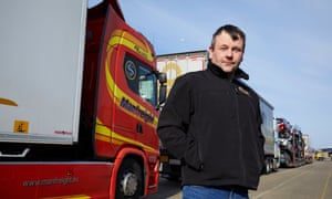 Stephen Connor in a zip-up jacket with his hands in his pockets, standing by his red and yellow lorry