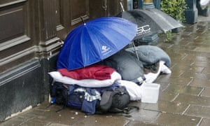 Belongings of homeless person under umbrellas in a rain storm