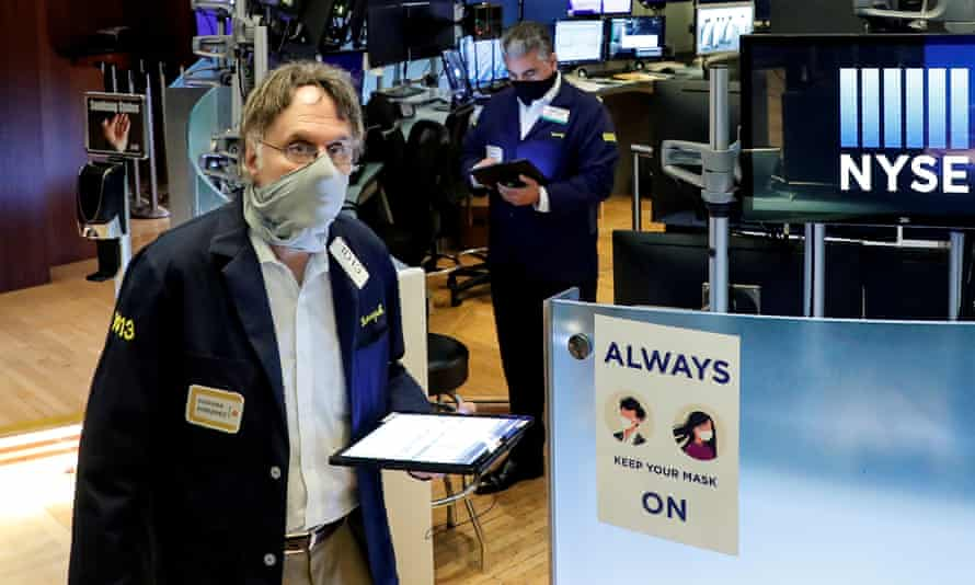 Traders wearing masks work on the floor at the New York Stock Exchange (NYSE) in New York