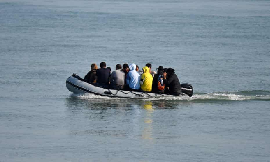 Migrants travel by inflatable boat as they reach the shore near Deal on the south east coast of England.