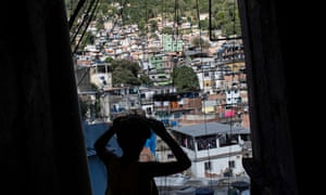 A boy walks through the Rocinha favela in Rio de Janeiro on 13 August 2016, where residents are still waiting for infrastructure promised under a federal investment programme.