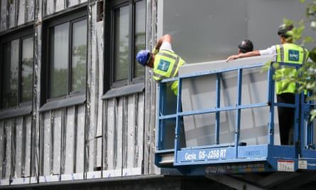Workers remove cladding for testing at a tower block in Salford.
