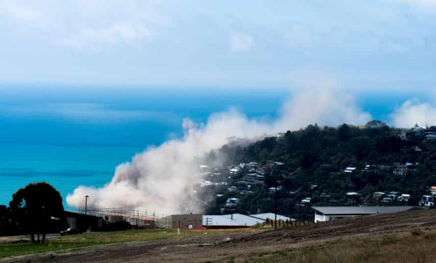 Dust and debris rise above houses after a cliff collapsed due to an earthquake above Scarborough Beach in the suburb of Sumner in Christchurch.