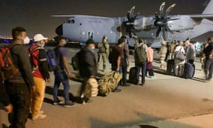 French and Afghan nationals line up to board a French military transport plane at the Kabul airport