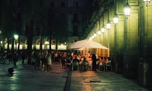 People eating outside at night in Barcelona.