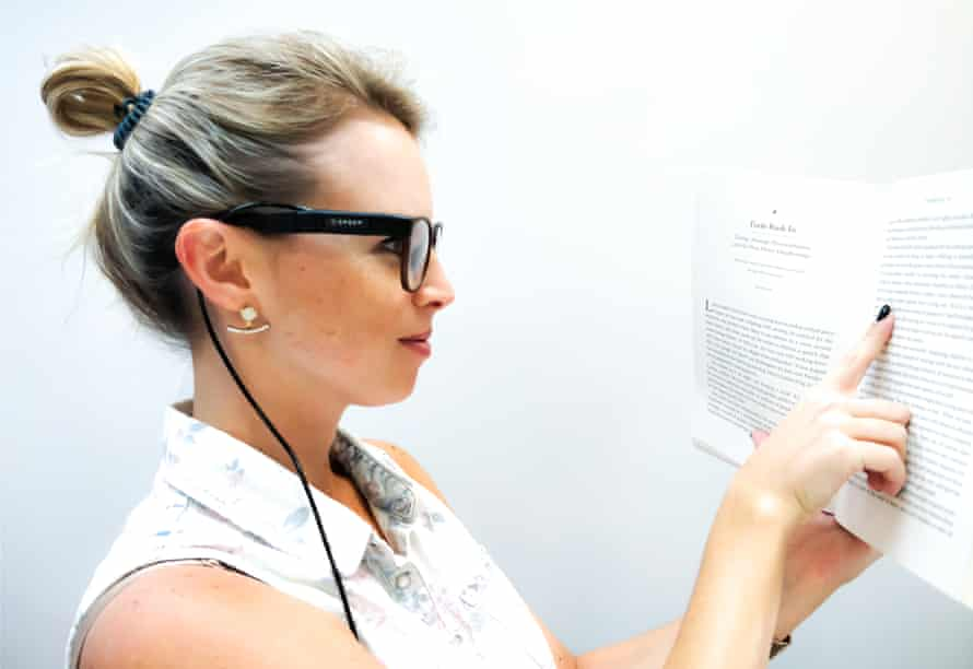 a young woman in profile using the orcam myeye device on her glasses to read from a book