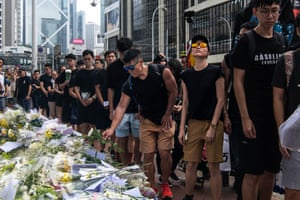 Mourners place flowers at the site where a protester died, prior to the start of a rally
