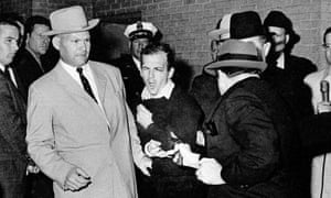 Lee Harvey Oswald, suspected assassin of President Kennedy, grimaces as he is shot to death at point-blank range by nightclub owner Jack Ruby in the basement of the Dallas police headquarters on 24 November 1963.