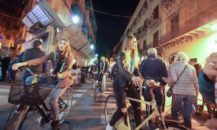 A night view of cyclists riding in Via Maqueda in Palermo