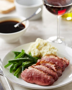 Duck breast served with mashed potato and green beans. Glass of red wine and sauce on background.
