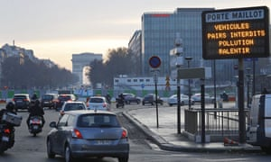Cars pass an information screen announcing driving restrictions as part of anti-pollution measures in Paris.