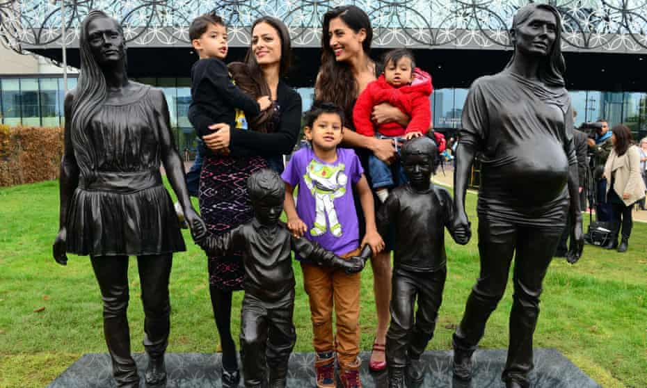 Roma Jones and her family with The Jones Family, a sculpture by Gillian Wearing in Centenary Square, Birmingham