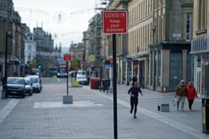 Covid-19 signage and a morning jogger in Newcastle city centre