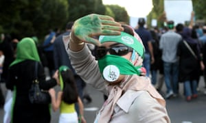 A Green movement supporter covers her face with piece of cloth and a sign in Persian with the name of an opposition leader Mir Hossein Mousavi at a 2009 rally in Tehran.