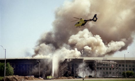 A helicopter flies over the Pentagon in Washington, Tuesday, Sept. 11, 2001 as smoke billows over the building. The Pentagon took a direct, devastating hit from an aircraft and the enduring symbols of American power were evacuated as an apparent terrorist attack quickly spread fear and chaos in the nation's capital. (AP Photo/Heenson Yim)