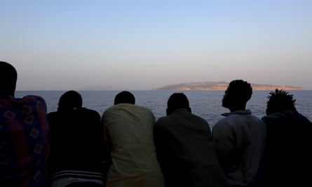 Migrants look out from a rescue ship