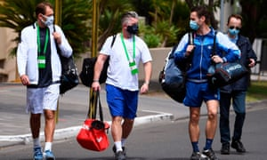 Polish tennis player Lukasz Kubot (L), trainer Hermanus Kroes (C) and Brazilian tennis player Marcelo Melo (2nd R) leave hotel for training session in Melbourne, 18 January 2021.