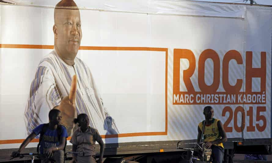 People stand in front of a campaign poster for Burkina Faso presidential candidate Roch Marc Kabore in Ouagadougou.