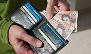 Man taking new ten pound notes from wallet