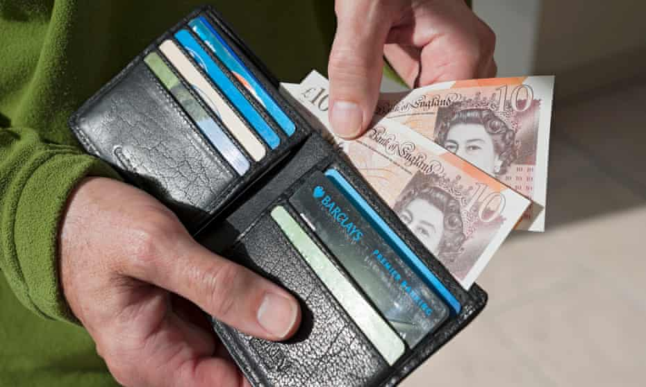 Man taking new £10 notes from wallet