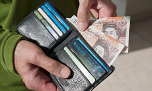 Man taking £10 notes from wallet