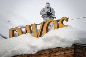 Davos, SwitzerlandA policeman wearing camouflage clothing stands on the rooftop of a hotel, next to letters covered in snow reading 'Davos', near the Congress Centre ahead of the World Economic Forum (WEF) annual meeting