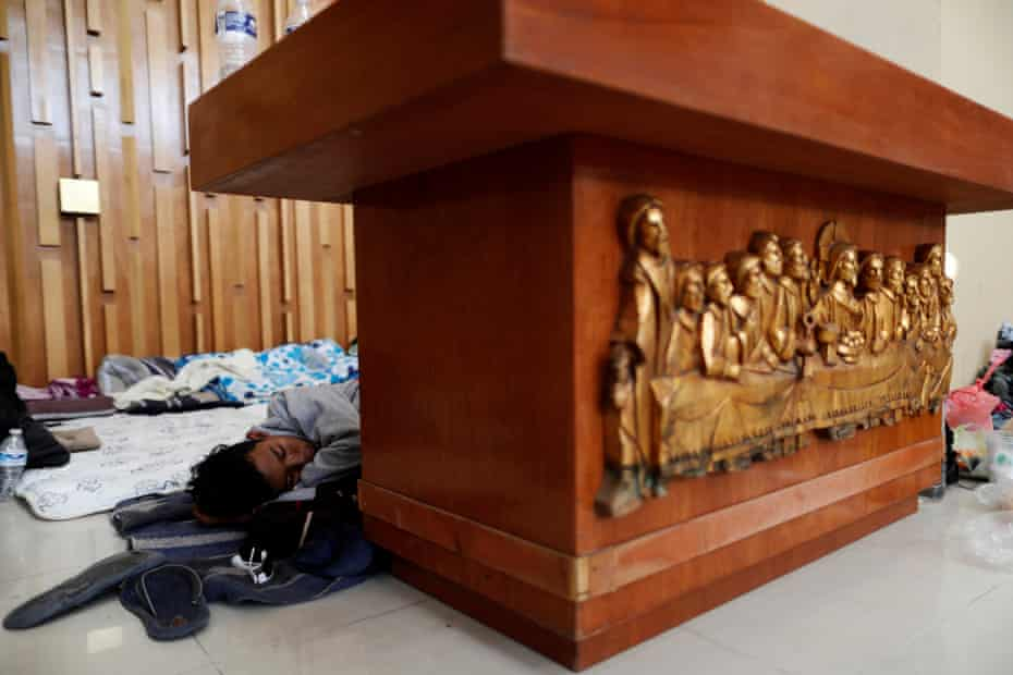 A Central American migrant, moving in a caravan through Mexico, sleeps behind an altar inside a Catholic church which also serves as a temporary shelter, in Tlaquepaque, Jalisco state 18 April