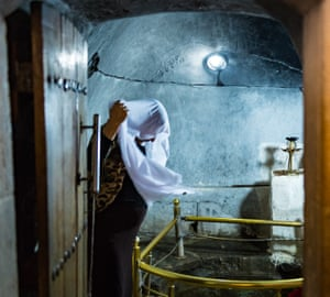 A woman covers her head with a white headscarf which has been bathed in the sacred spring.
