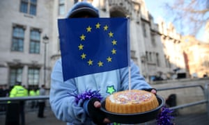 A demonstrator holds a cake with an EU flag in it outside the supreme court.
