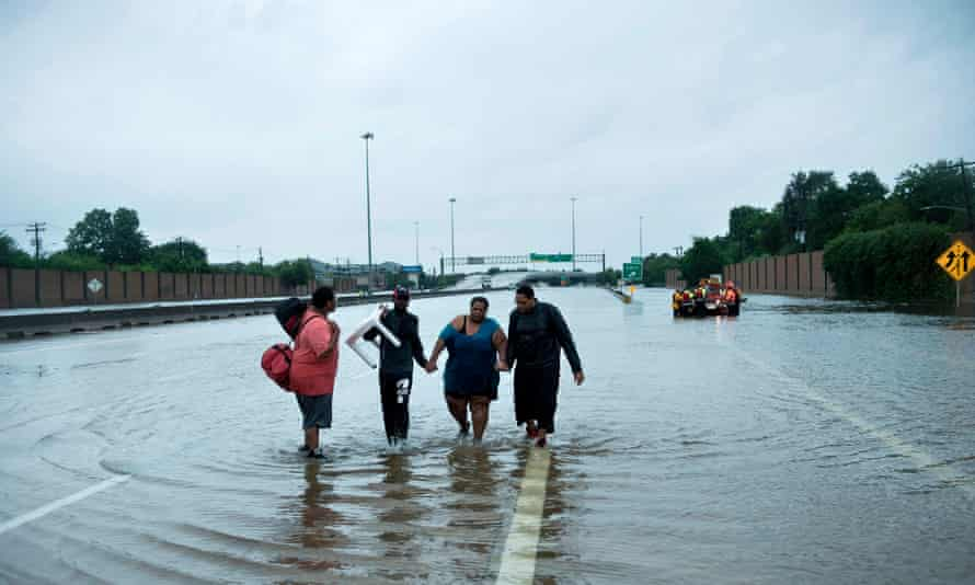 People make their way onto an I-610 overpass after being rescued from flooded homes during the aftermath of Hurricane Harvey, on 27 August 2017 in Houston, Texas.