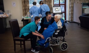 Care home resident Vera Levick, 106, is comforted by staff before receiving an injection of the coronavirus vaccine at Andrew Cohen House in Birmingham.