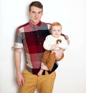 Seamas O'Reilly in a red checked shirt holding his smiling baby son in one arm