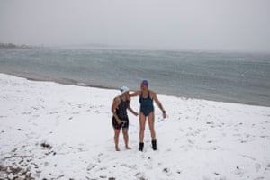 Two swimmers are seen on a snow-covered beach in the suburb of Glyfada.