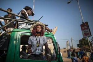An Adama Barrow supporter looks on from a van, as others gather in the streets on the outskirts of Banjul.