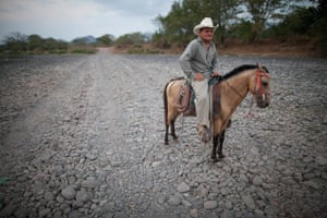 Oscar Alexis Maldonado Ramírez rides his horse Palomo along a dry stretch of the Río Nacaome