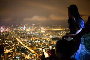 Pro-democracy activists look out over Hong Kong while forming a human chain on Lion Rock.