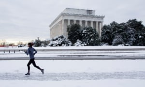 A jogger runs on a snow-covered sidewalk outside the Lincoln Memorial. The shutdown on Monday continued into its 24th day.