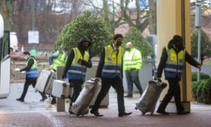 Workers carry passengers' luggage to a Holiday Inn hotel near Heathrow airport on Tuesday after new quarantine measures were brought in.