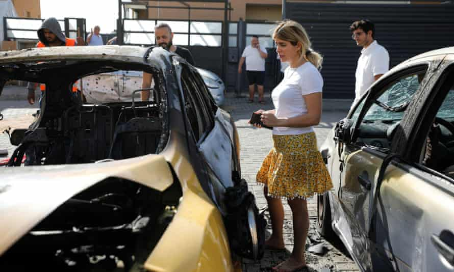 People look at a damaged car at a site where a rocket fired from Gaza landed in Ashkelon, southern Israel